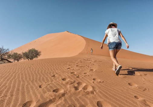 Girls Climbing Red Dune, Namibia. Sossusvlei.